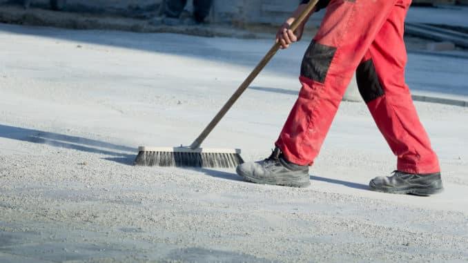 Mann in Arbeitsschuhen fegt Straße