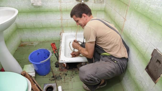 Handwerker reinigt verstopften Duschabfluss
